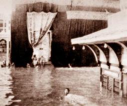 صورة قديمة للكعبة اثناء السيل المشهور بسيل الاربعاء ويظهر احد الحجاج وهو يسبح في الماء